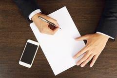 Les mains de l'homme d'affaires écrivent sur la feuille de papier blanche, plan rapproché de vue supérieure images stock