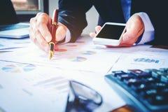 Les mains de l'homme d'affaires avec la calculatrice au bureau et financier Images libres de droits