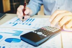 Les mains de l'homme d'affaires avec la calculatrice au bureau et financier Photo stock