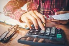 Les mains de l'homme d'affaires avec la calculatrice et le coût au bureau et au F Photographie stock libre de droits