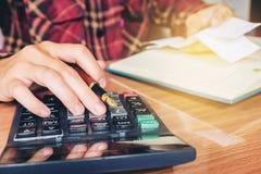 Les mains de l'homme d'affaires avec la calculatrice et le coût au bureau et au F Image libre de droits