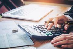 Les mains de l'homme d'affaires avec la calculatrice et le coût au bureau et au F Images stock