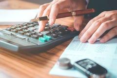 Les mains de l'homme d'affaires avec la calculatrice et le coût au bureau et au F Photos libres de droits