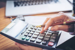 Les mains de l'homme d'affaires avec la calculatrice et le coût au bureau et au F Image stock
