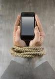 Les mains de l'homme d'affaires dépendantes à la corde de téléphone portable collent des poignets dans la dépendance d'Internet d photo stock