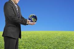 Les mains de l'homme d'affaires deux tiennent la boule avec la carte globale avec le vert frais Image libre de droits