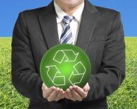 Les mains de l'homme d'affaires deux tiennent la boule verte avec réutilisent le symbole avec g Photos stock