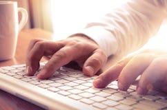Les mains de l'homme dactylographiant sur le clavier d'ordinateur Photographie stock libre de droits