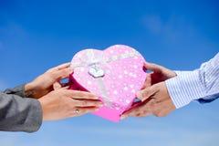 Les mains de l'homme donnant la boîte en forme de coeur rose à la femme Photo libre de droits