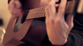 Les mains de l'homme jouant la guitare acoustique par le médiateur Foyer de Fretboard dedans  clips vidéos