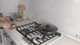 Les mains de l'homme ont coupé la saucisse sur un conseil en bois dans la cuisine près de la cuisinière à gaz banque de vidéos