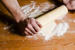 Les mains de l'homme ont roulé la pâte avec la goupille en bois sur la table en bois Images libres de droits