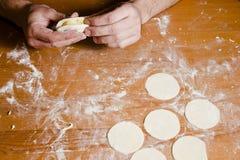 Les mains de l'homme préparant la pâte pour des ravioli, tortellini Photographie stock