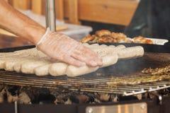 Les mains de l'homme, saucisses étendues pour les hot-dogs Photos stock