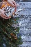 Les mains de l'homme tenant le boîte-cadeau de Noël sur le conseil bleu en bois avec c Photos stock