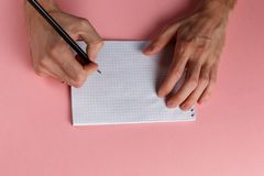 Les mains de l'homme tenant le crayon et le bloc-notes en spirale photo libre de droits