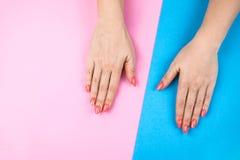 Les mains de la belle jeune femme sur le fond coloré images libres de droits