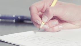 Les mains de la femme écrivant avec un crayon banque de vidéos