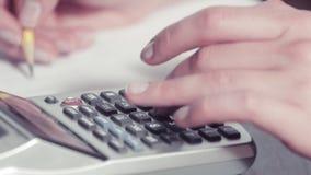 Les mains de la femme écrivant avec un crayon et dactylographiant sur une calculatrice banque de vidéos