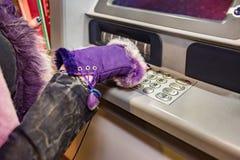 Les mains de la femme avec des gants tire dedans la carte de débit photographie stock libre de droits