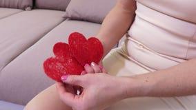 Les mains de la femme avec deux coeurs de papier rouges banque de vidéos