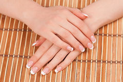Les mains de la femme avec la manucure française parfaite Image libre de droits