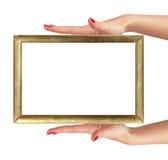Les mains de la femme avec le cadre d'or d'isolement sur le blanc images libres de droits