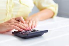 Les mains de la femme avec une calculatrice Photos stock