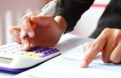 Les mains de la femme avec une calculatrice et un stylo Photographie stock