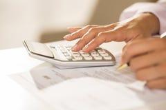 Les mains de la femme avec une calculatrice et un stylo, rendant compte. Photo stock