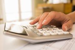 Les mains de la femme avec une calculatrice, rendant compte. Photographie stock