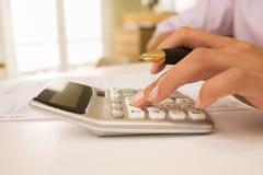 Les mains de la femme avec une calculatrice, rendant compte. Photo libre de droits