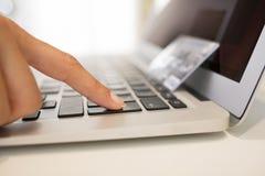 les mains de la femme avec une carte de crédit et un ordinateur d'utilisation Photos stock