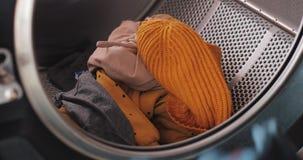 Les mains de la femme chargeant des vêtements à la machine à laver Blanchisserie publique de libre service banque de vidéos
