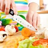 Les mains de la femme coupant des légumes Image libre de droits