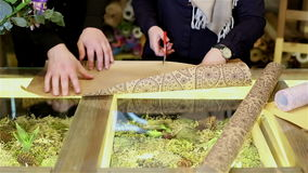 Les mains de la femme coupent le papier avec des ciseaux pour les fleurs de emballage clips vidéos