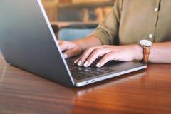 Les mains de la femme employant et dactylographiant sur le clavier d'ordinateur portable image libre de droits