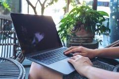 Les mains de la femme employant et introduisant au clavier sur le touchpad d'ordinateur portable tout en se reposant l'extérieur photographie stock