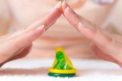 Les mains de la femme faisant le toit au-dessus du préservatif Photographie stock libre de droits