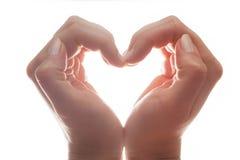 Les mains de la femme font une forme de coeur sur le fond blanc, contre-jour Amour Images libres de droits