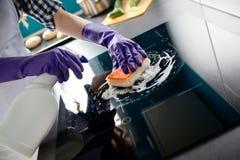 Les mains de la femme nettoyant la cuisine complètent dans les gants protecteurs images libres de droits