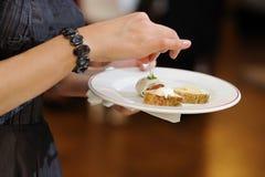 Les mains de la femme retenant une plaque avec des casse-croûte Photos stock
