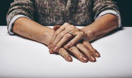 Les mains de la femme supérieure étreintes sur une table Photos libres de droits