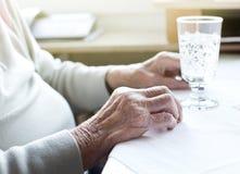Les mains de la femme supérieure avec le verre de l'eau Image stock