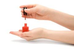 Les mains de la femme tenant une bouteille de vernis de clou Image libre de droits