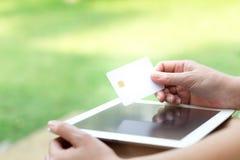 Les mains de la femme tenant une carte de crédit et à l'aide de la tablette image stock