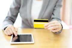Les mains de la femme tenant une carte de crédit et à l'aide de la tablette Images stock