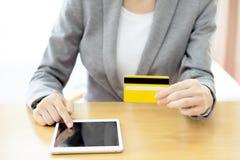 Les mains de la femme tenant une carte de crédit et à l'aide de la tablette Photographie stock libre de droits