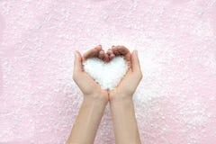 Les mains de la femme tiennent la neige, concept d'hiver Coeur photos libres de droits