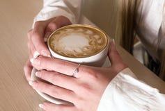 Les mains de la fille conserve le café de cuvette Photo libre de droits